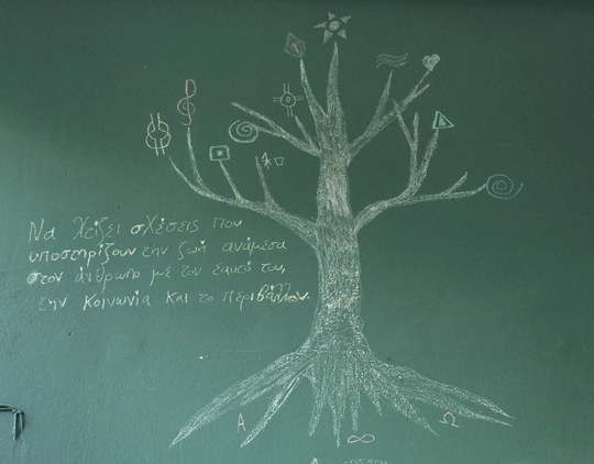 "Drawing of a tree in Plato's Academy Café. The Greek text reads: ""Build relationships that support life between humans and their selves, society, and nature."""